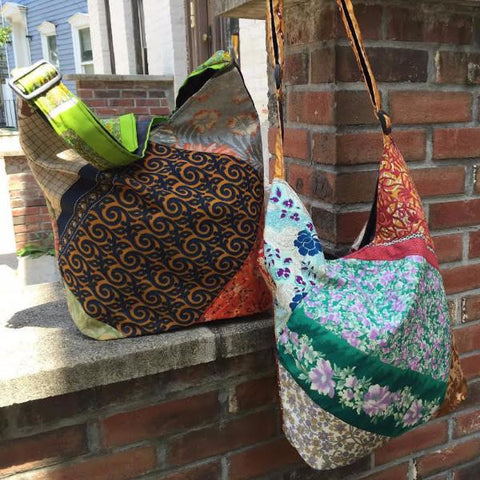 2 One of a Kind Sari Silk Purses hanging on a brick wall