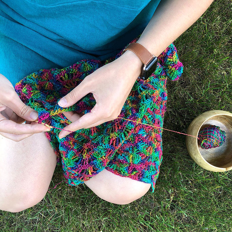 Woman's hands making Lace Weight Yarn Rainbow Shawl Crochet Project