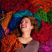woman smiling and laying on top of yarn