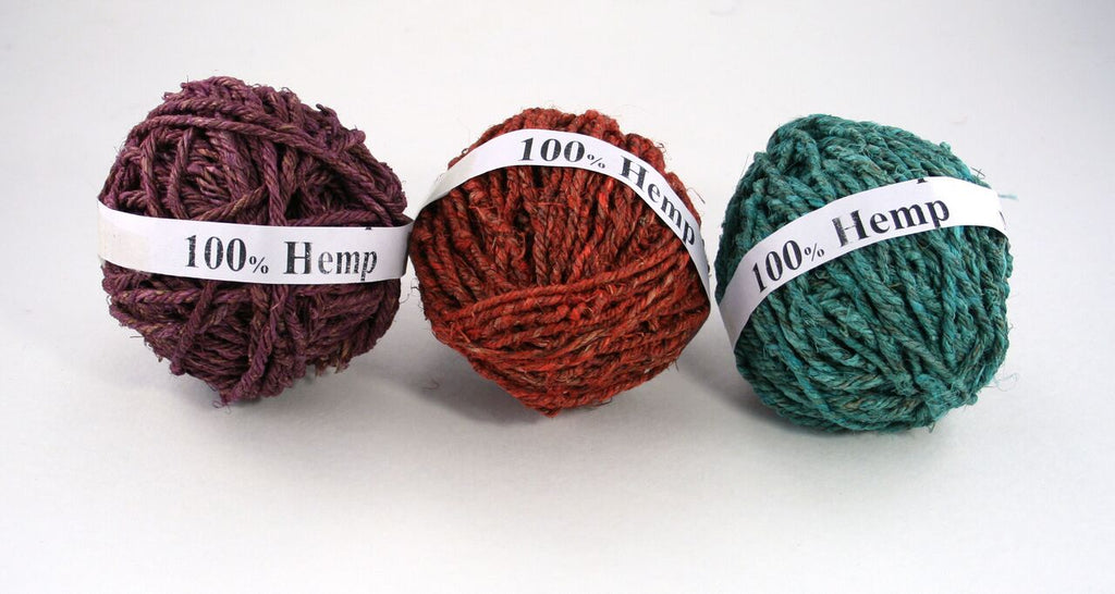 3 balls of hemp yarn in purple, rust, and teal sitting on a white background