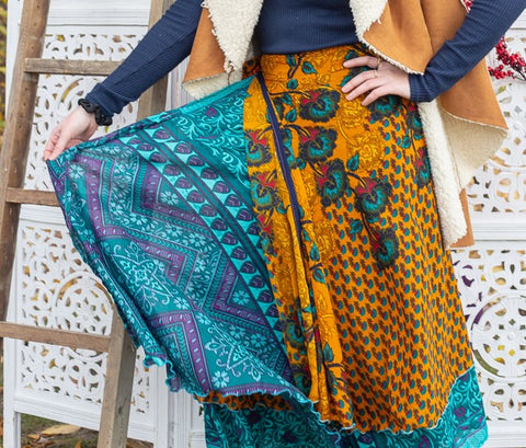 Close up of woman wearing a sari wrap skirt in front of a white lattice background