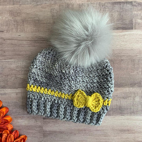 Gray and yellow winter hat on wood background with fuzzy gray pom pom