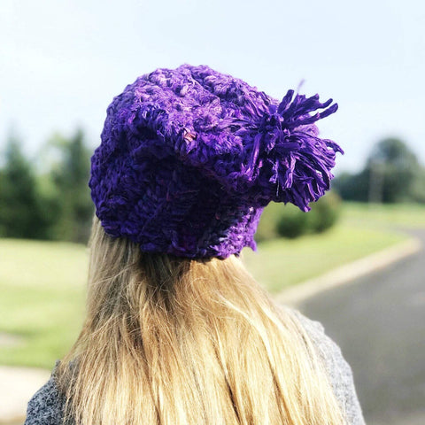 Woman wearing Sari Silk Ribbon Beanie in purple and standing in front of a grassy area