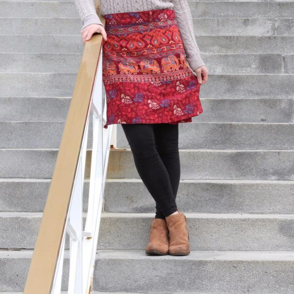 Woman standing on a concreted staircase wearing a red patterned cotton mini skirt, black tights, and brown booties and leaning against a white railing