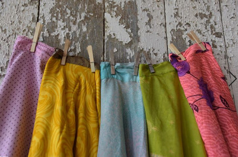 A yellow, blue, green, and pink skirt hang off a cloths line, held by clothespins, against a wooden wall with chipping white paint.