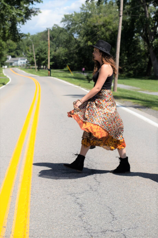 Woman wearing a sari wrap skirt, tank top, hat, and booties walking across a street