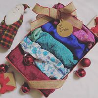 Gift box full of 5 multicolored Sari Wrap Skirts, tied with a gold bow, and sitting on a white surface next to red Christmas ornaments and a stuffed toy Santa