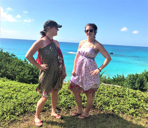 Two women wearing sari wrap skirts as dresses and standing on a hill overlooking an ocean