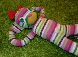 Multicolored striped knit monkey stuffed animal on a grass background