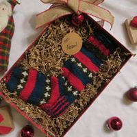 Gift box filled with brown paper confetti and a knitted Christmas Stocking, tied with a gold bow and sitting on a white background with several red Christmas ornaments and a stuffed Santa toy