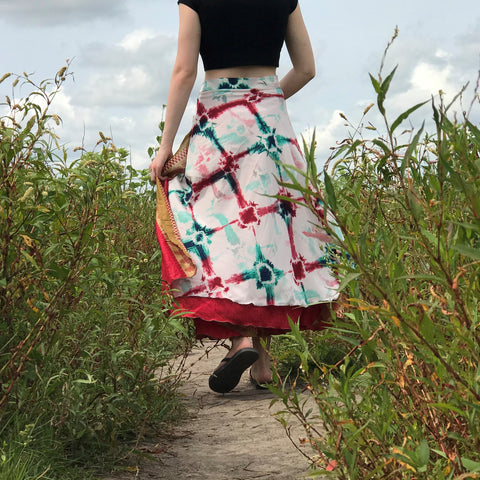 A person from their shoulders down, wearing a black crop top, a white-red-and-teal tie dyed skirt, walking down a dirt path, surrounded by long grass.