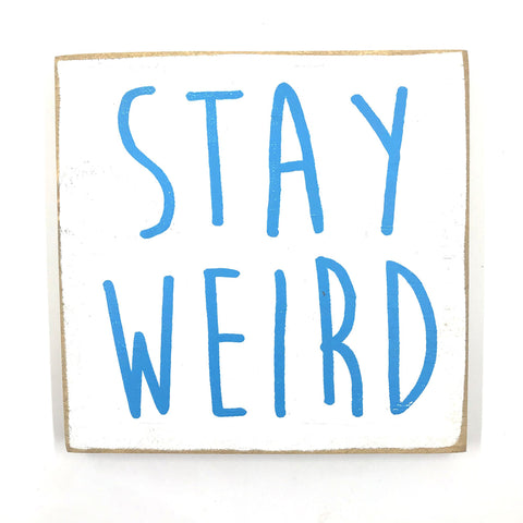 White wooden sign with blue text that reads 'Stay Weird'