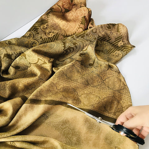 Cutting neutral colored sari fabric with scissors.