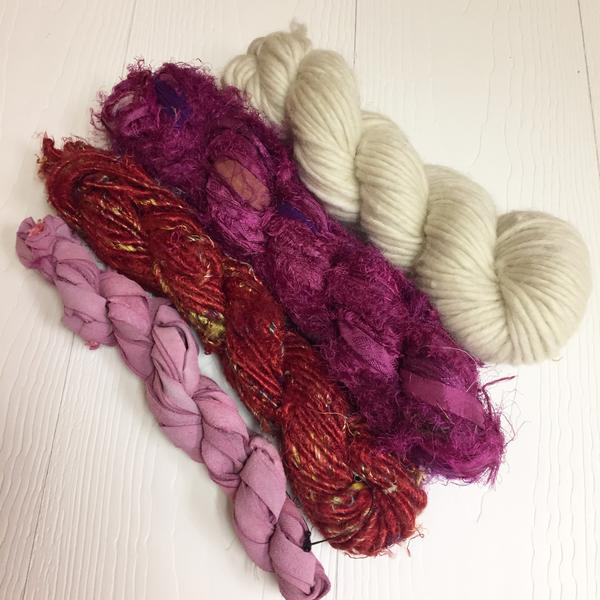 4 skeins of pink, red, and white yarn on a white background