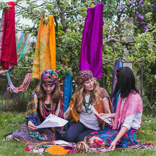 multiple women sitting over the grass wearing colorful clothes