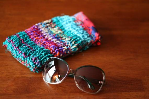 Pair of large sunglasses sitting on a wooden surface next to a knitted blue sunglasses case