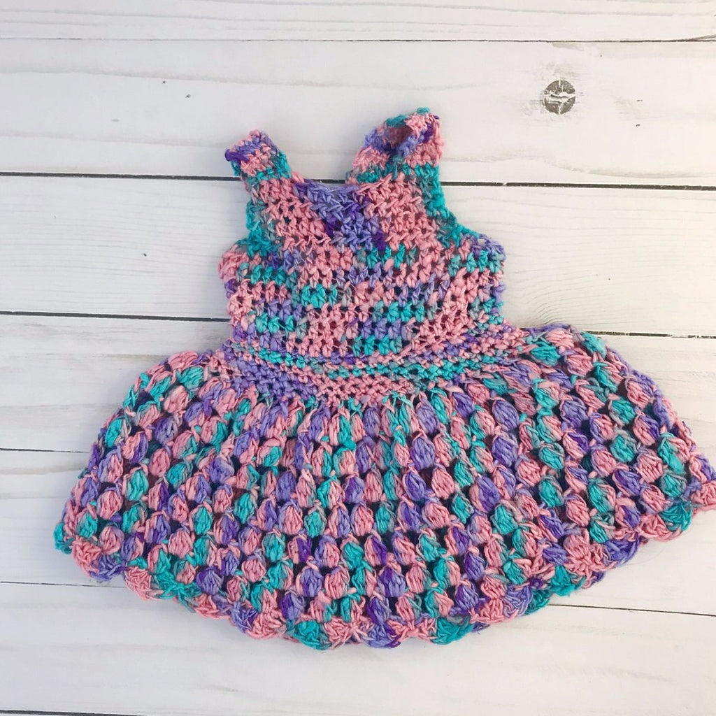 Pink, blue, and purple crochet sundress for a doll laid on a white wooden background