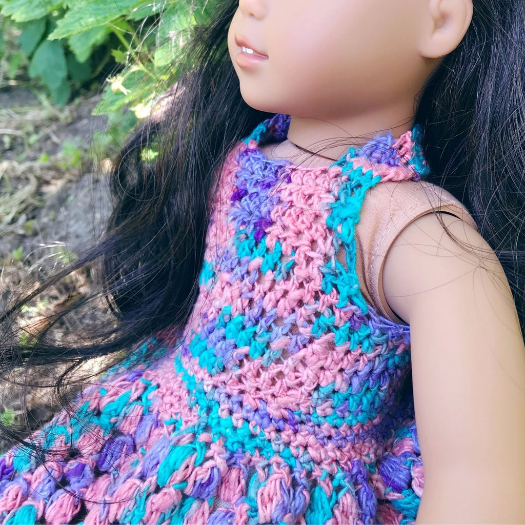 "Close up of an 18"" doll with dark hair wearing a pink, blue, and purple crochet sundress"
