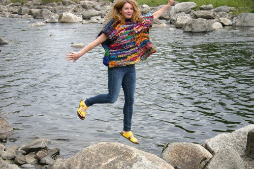 woman wearing a yarn sweater on top of a rock