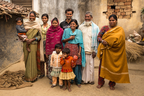 An Indian family poses for a family photo. The family, young and old, are dressed in beautiful clothing and make a handsome looking group. They are posting outdoors, on bare dirt, beside a terracotta-tiled roof hut.