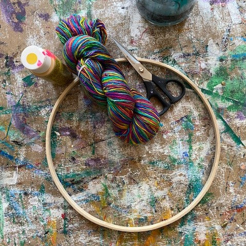 An unpainted wooden hoop is laying ontop of a brown artist's board that is heavily stained with paint. To the top of the hoop sits a small bottle of paint, a pair of scissors, and a hank of multicolored yarn.