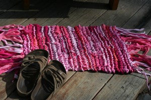 small pink yarn rug with slippers