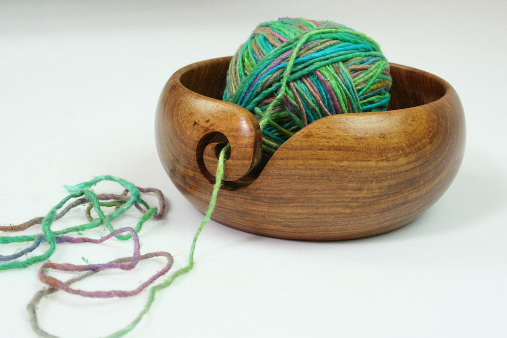 yarn bowl with yarn over a white background