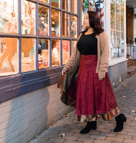 Woman wearing a sari wrap skirt and oversized cardigan while walking down a street looking into a shop window