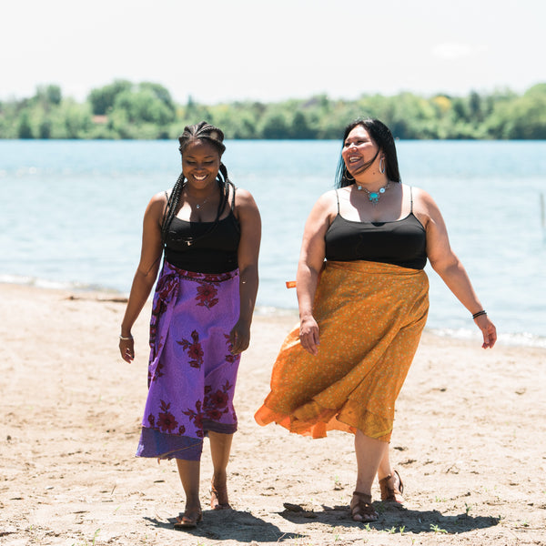 Recycled Indian Wrap Skirts worn by women on a beach