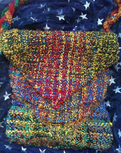 Multicolored woven messenger bag sitting on a fabric surface of navy blue with silver stars