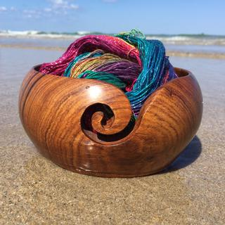 Wooden yarn bowl holding a multicolored ball of sparkly yarn sitting on a sandy beach in front of the water