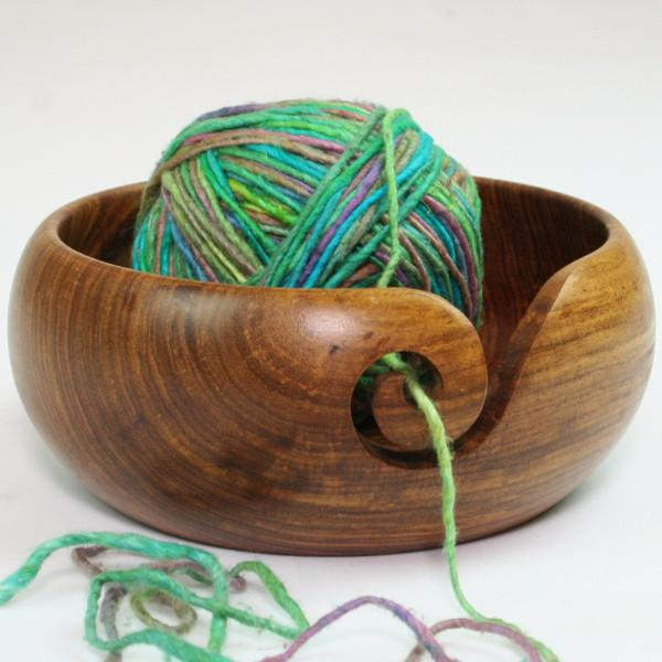Wooden yarn bowl holding a green ball of yarn while sitting on a white surface