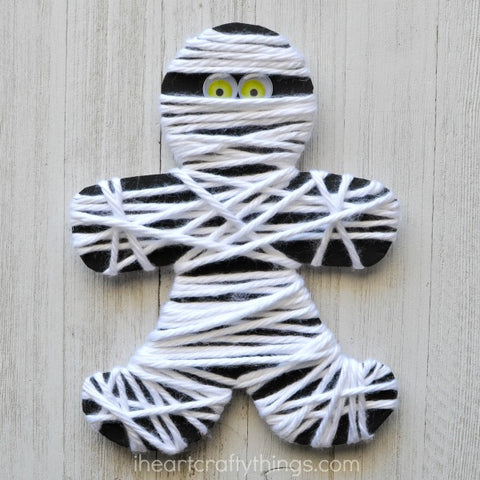 Paper and yarn mummy with googly eyes sitting on a wooden surface