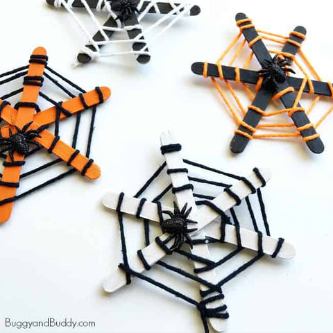 3 Popsicle stick and yarn spider webs with plastic spiders sitting on a white surface