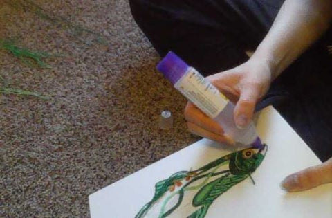 While sitting on the ground, the person is now using a glue-pen to glue the yarn onto the canvas board. The glue is placed in specific areas to create the pattern needed for the yarn painting.