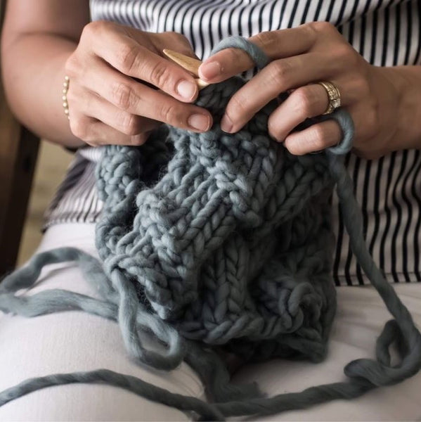 Woman's hands knitting a gray project