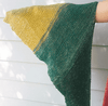 Woman's arm holding out a triangular green and yellow striped shawl