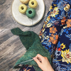 bird's-eye-view of woman wearing blue floral pants and knitting a shawl with green and yellow yarn cakes while sitting on a wooden surface
