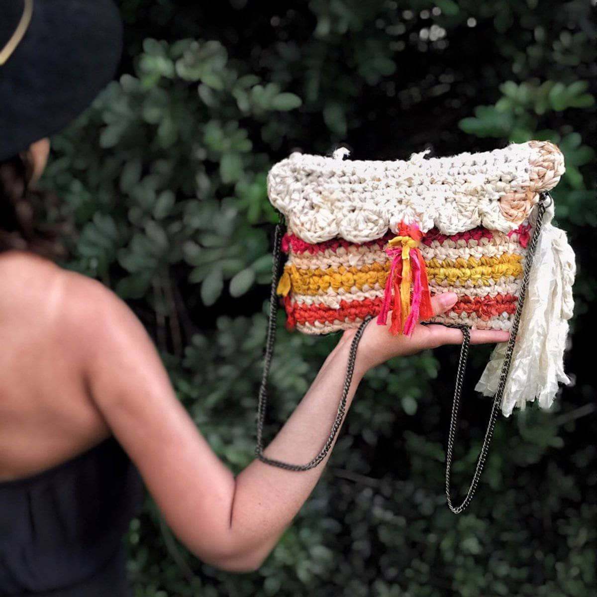 Back view of woman wearing a black hat and holding up a Sun Burst Clutch in front of greenery