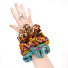 5 unique scrunchies being worn on the wrist of a pale arm wearing rings in front of a white background. Scrunchies pictured are earthy tones with a pop of purple and blue.