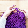Woman's hands making the Violet Summer Tote Crochet Kit on a wooden background
