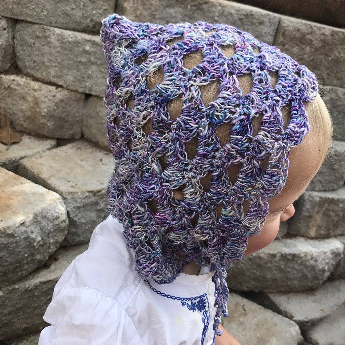 Baby wearing a purple Pixie Bonnet in front of a stone wall