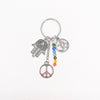 Chakra charm keychain on white background. Charms from left to right: hamasa (open hand), peace sign, chakra colored beads (rainbow), and Om (aum) charm.