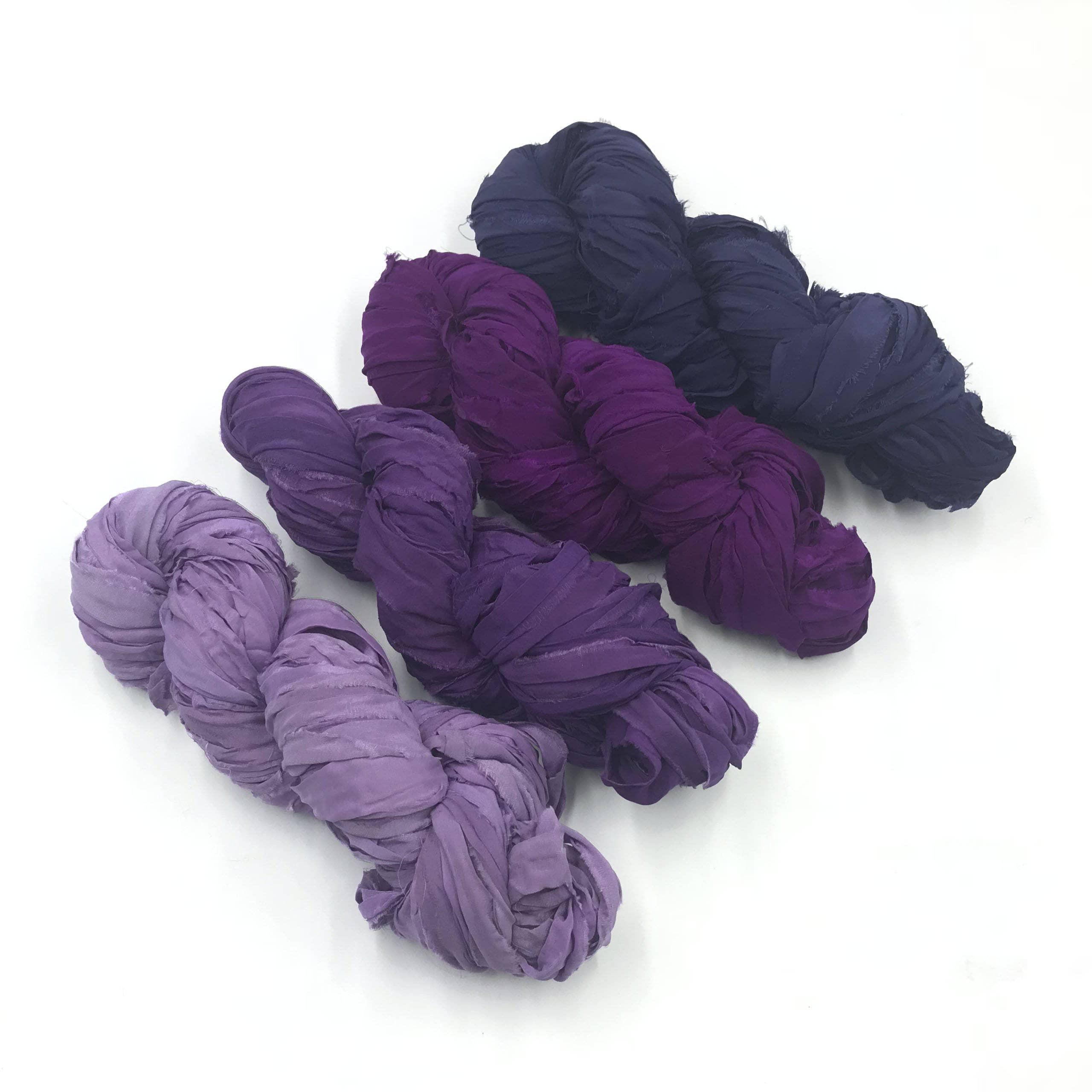 multiple lengths green Mountain Mist Handspun Art Yarn is a blue and purple fiber blend plyed with silver sequin thread