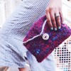 A woman holding a purple, pink and blue multicolored purse made from sari silk yarn on a white background