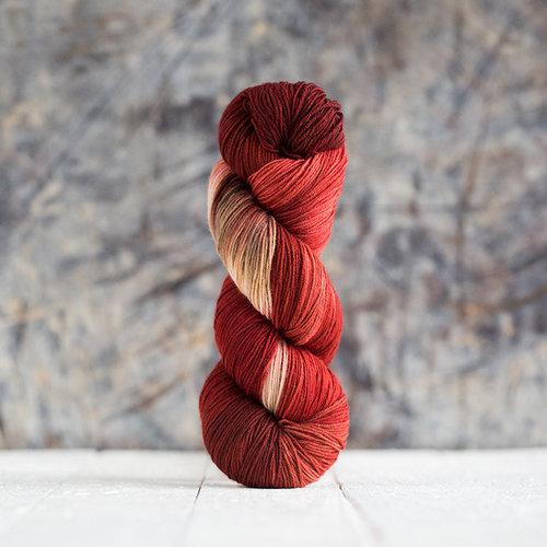 Dark red, red, and tan skein of yarn standing up on a marbled backdrop