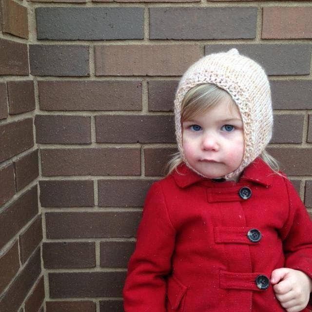 Little girl wearing a Merino Wool Baby Hoodie Hat and a red coat standing in front of a brick wall