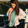 woman looking down wearing a colorful crochet scarf