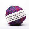 "close up of a multicolored cake of yarn with a white tag which reads ""Premium Sari Silk Handspun Yarn"""