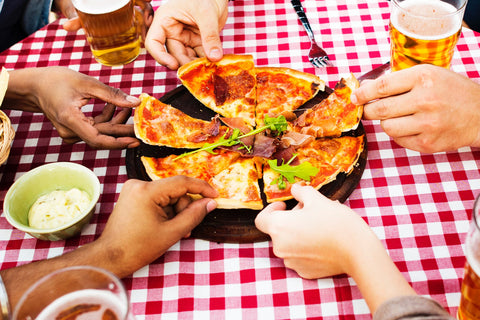 hands of people taking a slice of pizza at the dining table